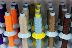 Shelf with multi-colored skeins of thread. Watching different colors of threads in sewing workshop royalty free stock photos
