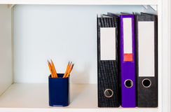 Shelf with office folders and pencil holder Royalty Free Stock Photos