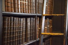 Shelf of old books in library. Detail picture of one of the bookshelves in the Long Room at Trinity College in Dublin, Ireland stock images