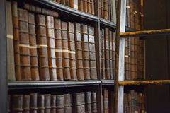 Shelf of old books in library. Detail picture of one of the bookshelves in the Long Room at Trinity College in Dublin, Ireland Stock Photo