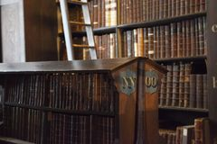 Shelf of old books in library. Detail picture of one of the bookshelves in the Long Room at Trinity College in Dublin, Ireland stock photography