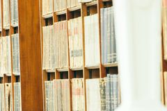 Shelf in an old library setting with old books on the shelf royalty free stock image