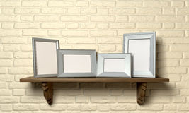 Shelf With Picture Frames Front. A front view of a regular wooden shelf displaying 4 blank metal picture frames on a yellow brick wall royalty free stock photo
