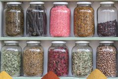 Shelf with preserving glasses. Shelf with ten preserving glasses vontaininge herbs and spices stock photography