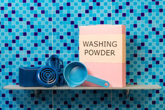 Shelf, ultrasonic washing machine, powder, measuring spoon on abstract blue. Stock Photography