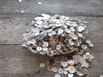 Shell Buttons in Silver Dish. Mother-of-pearl shell buttons in assorted sizes in a silver bowl on a gray barn wood table Stock Photos