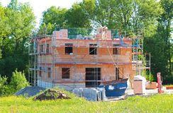 Shell construction in springtime landscape. Shell construction of a residential building in idyllic springtime landscape with large trees stock photography