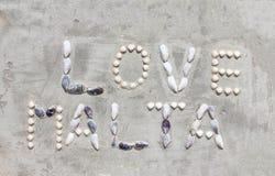 Shell-de brieven maken woordenliefde Malta op cementmuur stock afbeelding