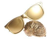 Shell dourado do mar e óculos de sol dourados Imagem de Stock