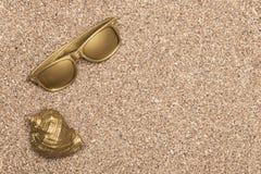 Shell dourado do mar e óculos de sol dourados Foto de Stock Royalty Free
