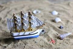 Shell e vela da areia no mar Imagem de Stock