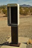 Empty telephone booth in desert outdated technology. Shell of an empty telephone booth for out-dated technology when pay phones were common, now stands alone and Stock Photo