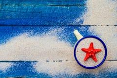 Shell foggia a coppa i bordi blu sparsi sabbia Immagini Stock