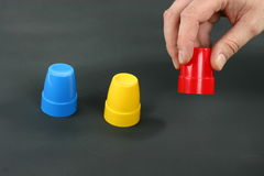 Shell game. Three inverted cups used in shell game with a hand lifting one Stock Image