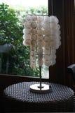 Shell hizo la lámpara en la tabla cerca de ventana imagen de archivo libre de regalías