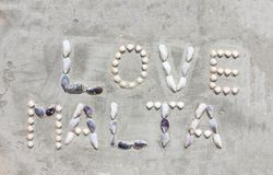 Shell letters make words Love Malta on cement wall stock image