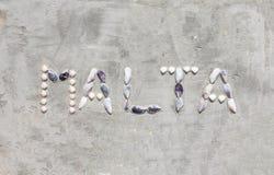 Shell listy robią słowu Malta na cement ścianie obrazy stock