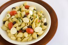 Shell Macaroni and chesse with tomato. Macarnoni Shells with Mozzarella cheese, tomato, black olives, in light olive oil.  A Healthy Pasta salad Royalty Free Stock Photography