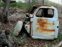 A shell of an old rusted blue motor vehicle. A shell of an old abandoned rusted blue motor vehicle lying in a forest stock image