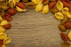 Shell pasta on wooden table top view frame Royalty Free Stock Photo