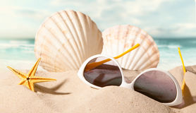 Shell with sunglasses on beach Stock Photo