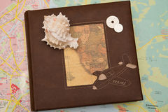 Shell on travel book. With maps background Stock Image
