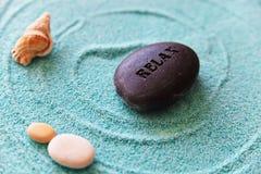 Shell und Stein entspannen sich auf einem blauen Sand Stockfoto