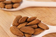 Shelled almonds on a spoon. And light wood Stock Photos