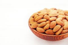 Shelled almonds in a wooden bowl on white background. Stock Photos