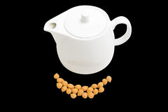 Shelled apricot kernels and ceramic teapot on a black background. Shelled apricot kernels and white ceramic teapot on a black background. Isolation Royalty Free Stock Photography