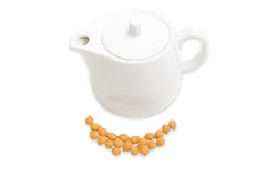 Shelled apricot kernels and ceramic teapot on a light background Stock Photos