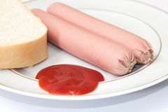 Shelled frankfurters on a plate with ketchup and bread Stock Image