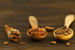 Shelled hazelnuts, roasted coffee beans, cinnamon on wooden background Royalty Free Stock Photos