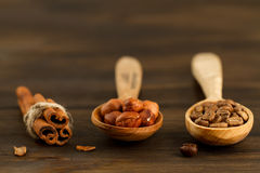 Shelled hazelnuts, roasted coffee beans, cinnamon on wooden background Stock Photos