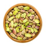 Shelled pistachio kernels in wooden bowl over white Royalty Free Stock Images