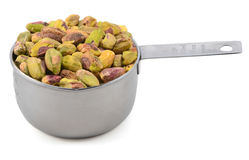 Shelled pistachio nuts in a metal cup measure Stock Photo