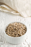 Shelled sunflower seeds in bowl on rustic white table Stock Image