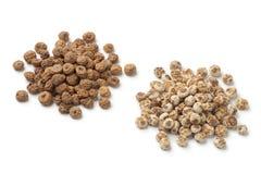 Shelled and unshelled Chufa nuts. Heap of shelled and unshelled Chufa nuts on white background Royalty Free Stock Photo