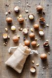 Shelled and unshelled Macadamia nuts on wooden board. Top view of shelled and unshelled Macadamia nuts on wooden board Royalty Free Stock Image