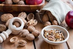 Shelled and unshelled walnuts on a wooden table. Shelled and unshelled walnuts with apples and a nutcracker on a wooden table Royalty Free Stock Photos
