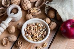 Shelled and unshelled walnuts on a wooden table with a nutcracke. Shelled and unshelled walnuts on a wooden table with an apple and a nutcracker Royalty Free Stock Photography