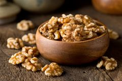Shelled Walnuts. A bowl of healthy delicious shelled walnuts on a rustic wooden table top Stock Images