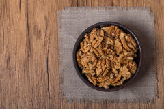Shelled walnuts in bowl on wooden background Royalty Free Stock Photography