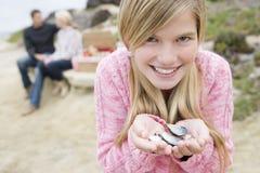 Shelles de la explotación agrícola de la muchacha en la playa Imágenes de archivo libres de regalías