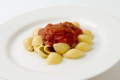 Shelles plateados de las pastas y salsa roja Foto de archivo