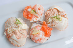 Shellfish Buffet. Prawns and smoked salmon in scallop shells garnished with dill and lemon Royalty Free Stock Photos