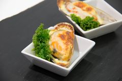 Shellfish mussels Baked  with cheese in shells served. Seafood Shellfish mussels Baked  with cheese in shells served Royalty Free Stock Photos
