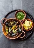 Shellfish Mussels in copper bowl, lemon, herbs sauce. Stock Photo