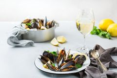 Shellfish mussels with white wine, seafood on a table. Still life, restaurant dinner. Shellfish mussels with lemon and green parsley with white wine. Seafood on Stock Photo