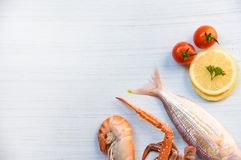 Shellfish seafood fish shrimp prawns and crab claws ocean gourmet dinner and tomato lemon. On white table background royalty free stock images